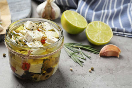 Composition with pickled feta cheese in jar on grey table, space for text