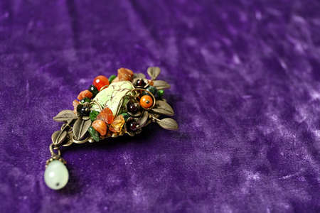 Beautiful brooch with gemstones on violet fabric. Space for text Stock Photo