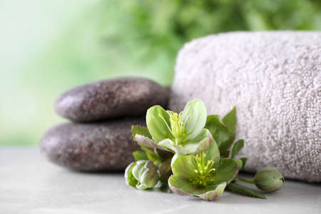Composition with flowers, spa stones and towel on grey table against blurred background
