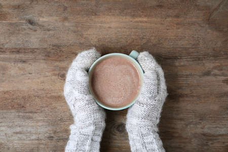 Woman with knitted mittens holding cup of delicious cocoa drink at wooden table, top view