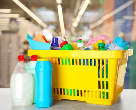 Shopping basket with different detergents on table in supermarket Standard-Bild