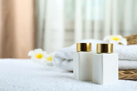 Composition with cosmetic products on white towel indoors, space for text. Spa therapy