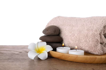 Tray with candles and spa supplies on wooden table against white background