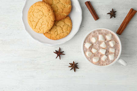 Composition with delicious hot cocoa drink and cookies on white wooden background, flat lay