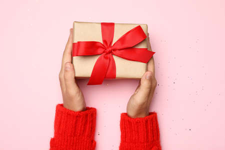 Young woman holding Christmas gift on pink background, top view Stock Photo