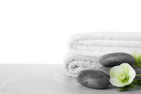 Towels, spa stones and flower on marble table against white background