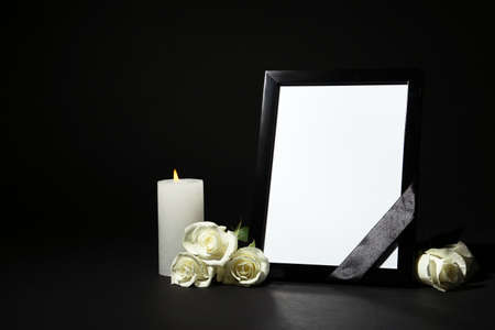 Funeral photo frame with ribbon, white roses and candle on dark table against black background. Space for design
