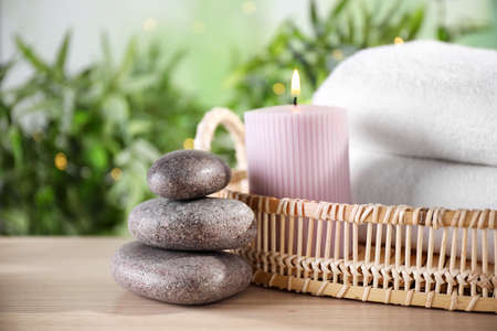 Spa stones and tray with towels and lit candle on wooden table, space for text