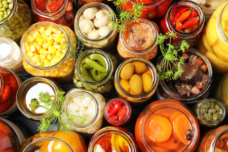 Open jars with pickled vegetables and dill inflorescences on grey table, flat lay