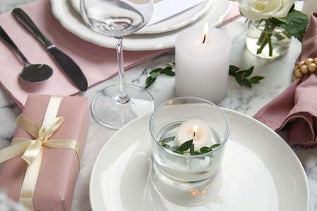 Elegant festive table setting on white marble background, closeup