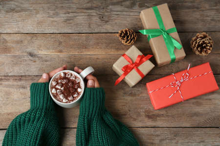 Woman holding cup of delicious cocoa drink at wooden table with Christmas presents, top view Zdjęcie Seryjne