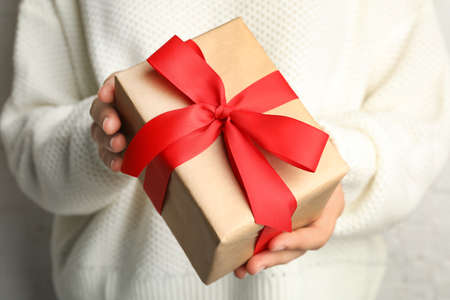 Young woman holding Christmas gift, closeup view