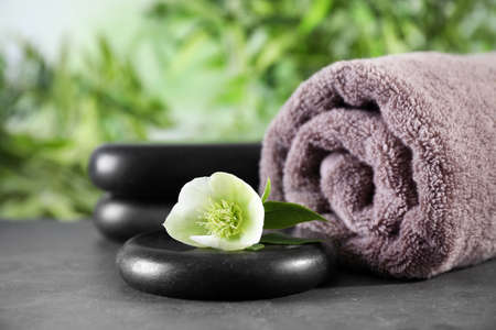 Composition with flower, spa stones and towel on black table against blurred background. Space for text Фото со стока