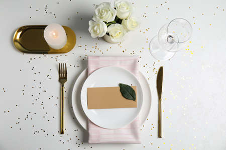 Elegant festive table setting with blank card on white background, flat lay