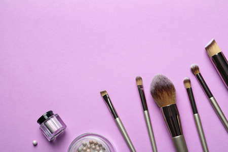 Flat lay composition with makeup brushes on lilac background. Space for text