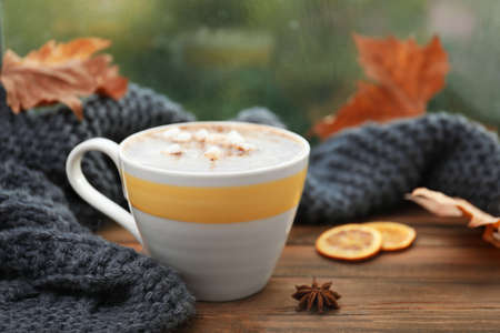 Cup of hot drink and scarf on window sill indoors. Cozy autumn atmosphere Zdjęcie Seryjne