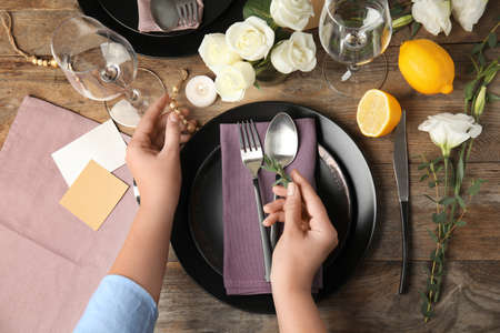 Woman setting table for festive dinner, top view Stock Photo