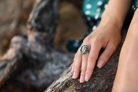Young woman wearing beautiful silver ring with prehnite gemstone outdoors, closeup, Space for text