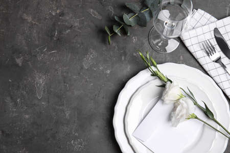 Elegant festive table setting on dark grey background, flat lay. Space for text
