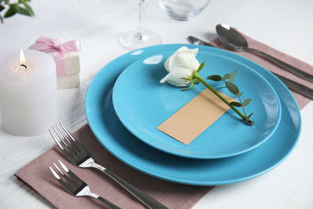Elegant festive table setting with blank card on white wooden table