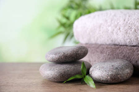 Composition with spa stones and towels on wooden table against blurred background. Space for text Фото со стока - 131844217