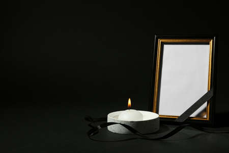 Funeral photo frame with ribbon and candle on black background. Space for design