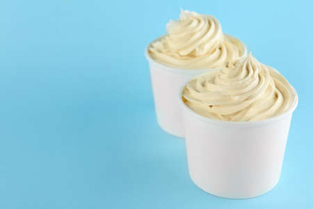 Cups with tasty frozen yogurt on blue background. Space for text Banque d'images - 131845019