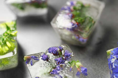 Ice cubes with flowers on grey stone table, closeup Banque d'images - 131844484