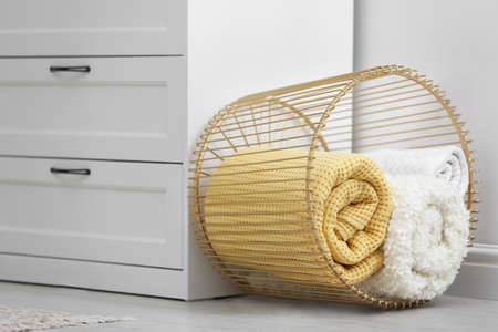 Basket with soft plaid near commode in room