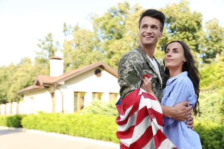 Man in military uniform with American flag hugging his wife outdoors