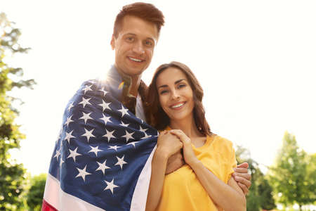 Man in military uniform with American flag and his wife at sunny park Banque d'images