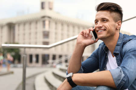 Portrait of handsome young man talking on phone outdoors. Space for text