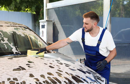 Young worker cleaning automobile with sponge at car wash Stok Fotoğraf