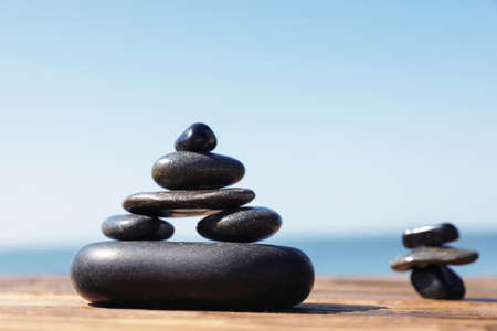 Stacks of stones on wooden pier near sea, space for text. Zen concept Zdjęcie Seryjne