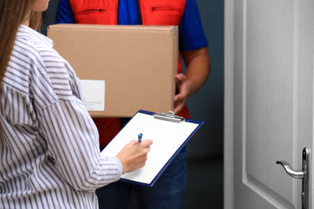 Woman signing for delivered parcel on doorstep, closeup