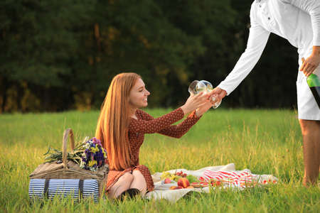 Young man giving wineglasses to his girlfriend in green park. Picnic season