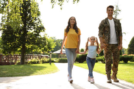 Man in military uniform and his family walking at sunny park