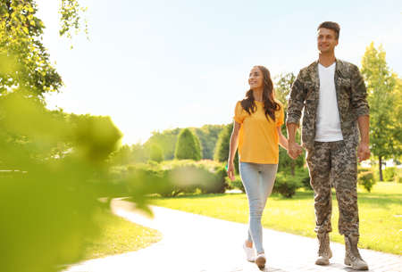 Man in military uniform walking with his girlfriend at sunny park