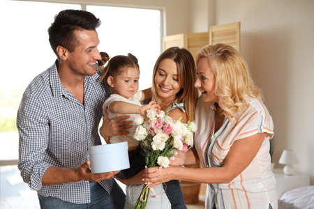 Happy family congratulating little girl at home