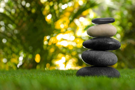Stack of stones on green grass against blurred background, space for text. Zen concept Zdjęcie Seryjne