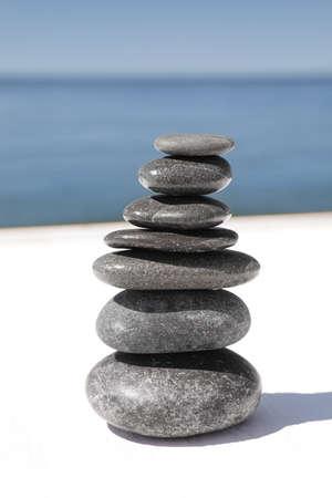 Stack of stones on wooden pier near sea. Zen concept