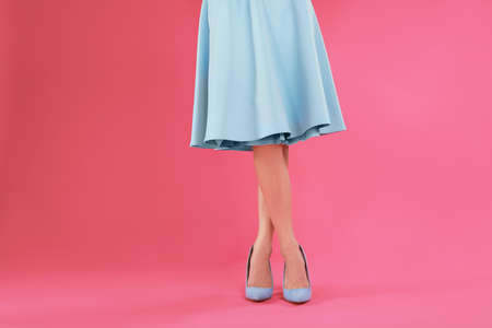 Woman in elegant shoes on pink background