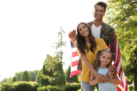Man in military uniform with American flag and his family at sunny park Archivio Fotografico
