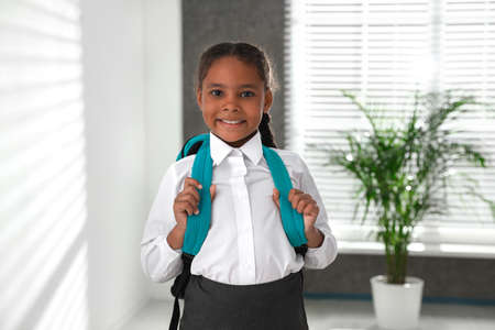 Happy African-American girl in school uniform with backpack indoors