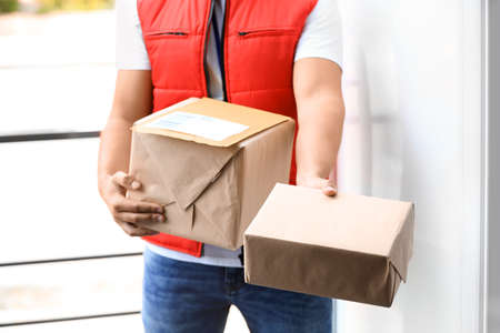 Young courier delivering parcels on doorstep, closeup 写真素材