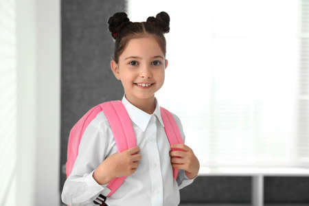 Happy girl in school uniform with backpack indoors