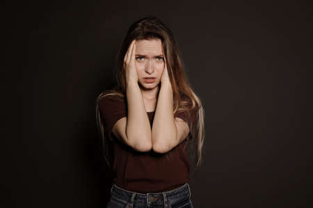 Portrait of upset young woman on dark background
