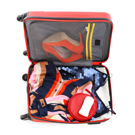 Packed suitcase with deodorant and clothes on white background, top view Foto de archivo