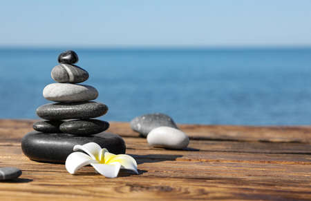 Stack of stones and flower on wooden pier near sea, space for text. Zen concept Zdjęcie Seryjne