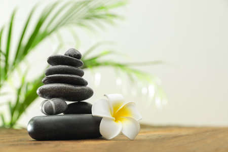 Table with stack of stones, flower and blurred green leaves on background, space for text. Zen concept